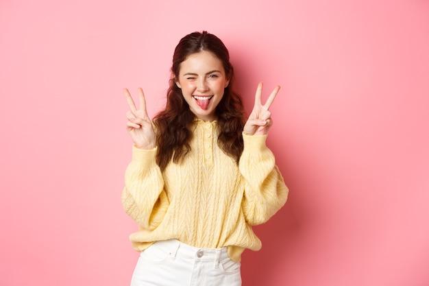 Милая и позитивная молодая женщина подмигивает, показывает язык, делает знак v и улыбается, приподнятая у розовой стены