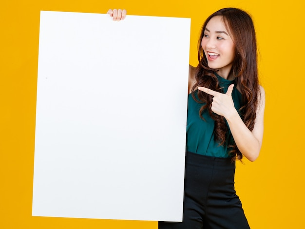 白い空白のボードを保持しているキュートでかわいい巻き毛のアジアの女性ブルネットは、広告やバナーの使用目的のために楽しい、明るい黄色の背景で隔離のスタジオショットでカメラにポーズします。
