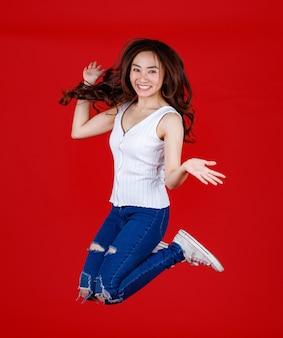 Симпатичные и довольно темные волосы азиатские женщины чувствуют себя взволнованными и прыгают в воздух с забавными и веселыми для рекламы и использования баннеров, замораживая стоп-движение, изолированное на ярко-красном фоне.
