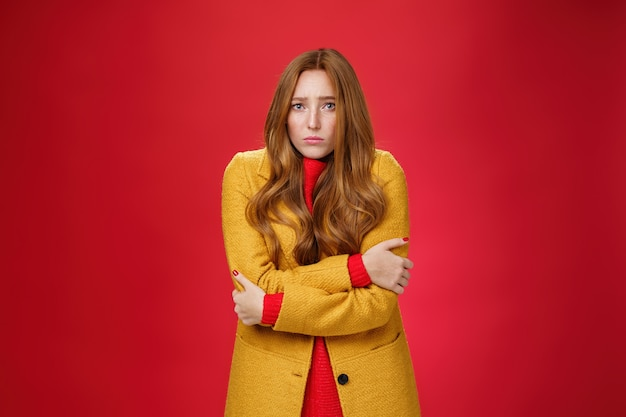 옅은 노란색 코트를 입은 귀엽고 슬픈 떨리는 빨간 머리 소녀는 추위에 떨고, 붉은 배경 위에 바람이 부는 날씨에 얼어붙는 것처럼 소름이 돋고 슬픔에서 삐죽삐죽합니다. 복사 공간