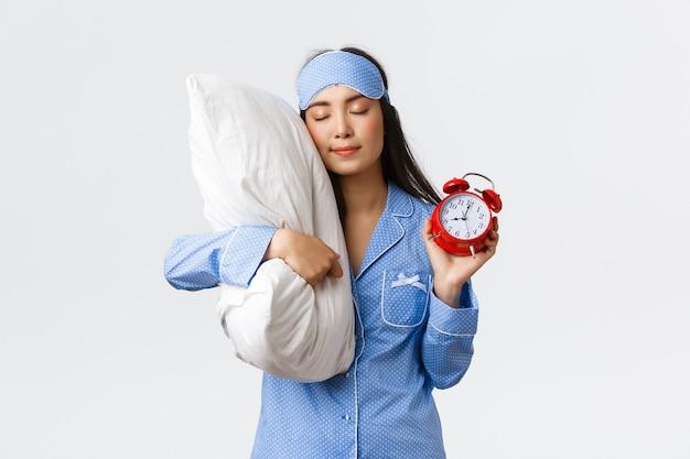 Симпатичная и глупая азиатская девушка в синей пижаме и спальной маске, спящая на подушке с закрытыми глазами и показывающая будильник, мечтающая о сладких снах, когда забыла установить будильник, белая стена
