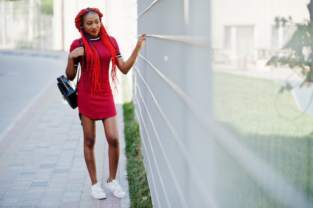 Симпатичная и стройная женщина в красном платье с дредами и рюкзаком на улице на фоне ворот в клетку