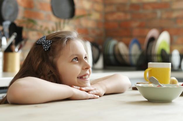 キッチン、朝食時間でかわいいと笑顔の女の子