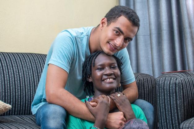 男性が女性を抱きしめている間、一緒に幸せに座っているキュートで笑顔の異人種間のカップル