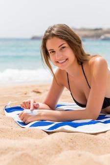 귀엽고 웃는 여자는 해변에서 수건에 일광욕 손가락으로 그녀의 손에 자외선 차단제를 적용하고 있습니다.
