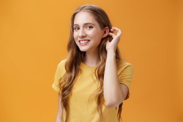귀여운 물결 모양의 헤어스타일을 한 귀엽고 부드러운 시시덕거리는 젊은 여성이 귀 뒤에서 머리카락을 쓸어 넘기며 주황색 배경 위에 있는 남자를 감탄하며 소심한 관능적인 미소로 카메라를 응시하고 있습니다. 복사 공간