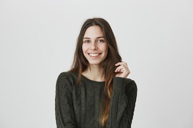 キュートで優しい笑顔の女性が彼女の髪に触れるとカメラを注視