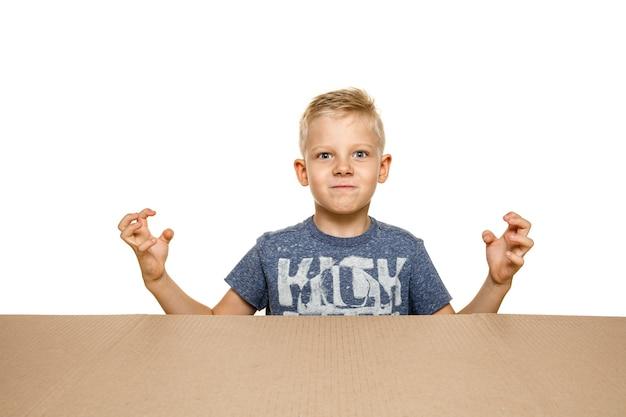 가장 큰 우편 패키지를 여는 귀엽고 화가 어린 소년. 내부보고 골 판지 상자 위에 실망 된 젊은 남성 모델.