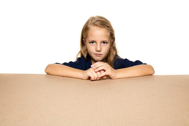 最大の郵便パッケージを開くキュートで動揺した少女 Premium写真
