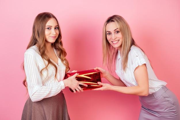 Милая и молодая дочь лица женского пола дает коробку с подарком маме на розовом фоне в студии. концепция празднования дня матери.