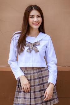 일본, 한국 스타일의 여학생 교복을 입은 귀엽고 어린 소녀가 학교 건물 앞에서 즐겁고 행복한 표정으로 카메라를 향해 포즈를 취하고 있습니다.