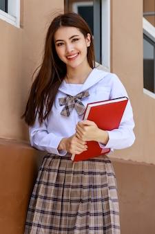 일본, 한국 스타일의 여학생 교복을 입은 귀엽고 어린 소녀가 책을 들고 학교 건물 앞에서 재미있고 행복하게 카메라에 포즈를 취합니다.