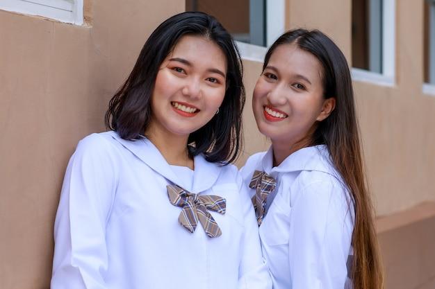 일본, 한국 스타일의 여고생 교복을 입은 귀엽고 어린 소녀들이 학교 앞에서 즐겁고 행복한 표정으로 카메라를 향해 포즈를 취하고 있습니다. 대학 개념에서 가까운 친구.