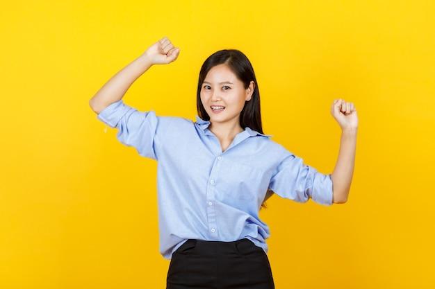 귀엽고 젊은 일본 스타일 소녀가 서서 손을 들고 노란색 배경에 웃는 얼굴로 주먹을 날립니다