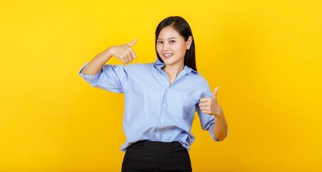 귀엽고 젊은 일본 스타일 소녀가 서서 손을 들고 노란색 배경에 웃는 얼굴로 엄지손가락을 보여줍니다.