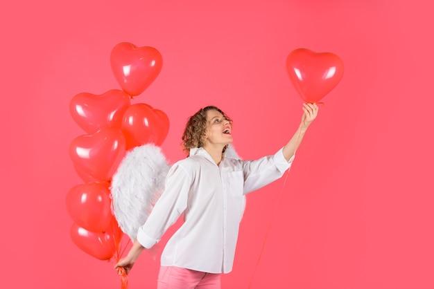 Милая девушка-ангелочка с красными сердечными воздушными шарами красивая девушка-ангел с красными воздушными шарами женщина-купидон с