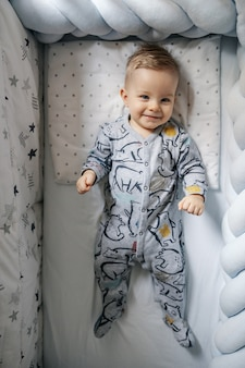 Cute angelic little blond baby boy lying down in his crib, smiling and waking up. morning time.