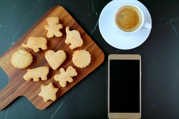 Милое печенье в форме животного с чашкой кофе и пустым экраном смартфона на черном мраморном столе