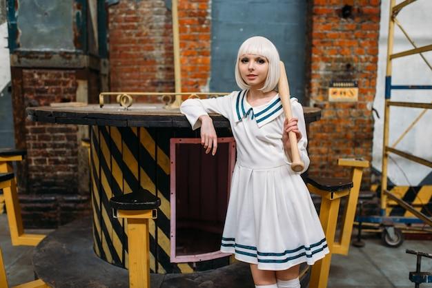 Cute anime style blonde lady with baseball bat. cosplay fashion, asian culture, doll in dress, sexy woman with makeup in the factory shop