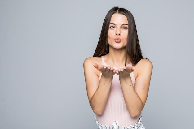 Carino accattivante donna soffia bacio, dimostra amore al fidanzato o dice addio a distanza, isolato sopra il muro bianco la giovane donna attraente mostra simpatia a qualcuno
