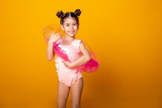 Милая арабская маленькая девочка в купальном костюме и плавательном надувном кольце, улыбаясь, весело на желтой поверхности.