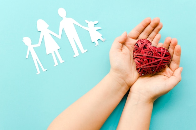 Cute arrangement of paper family on blue background with red heart