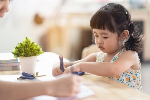 엄마와 함께 집에서 나무 탁자에 whte 종이로 그림을 그리는 귀여운 아시아 여자