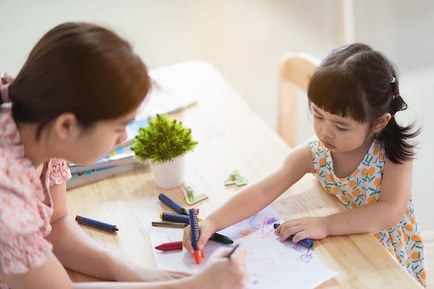 Милая азиатская девочка рисунок белой бумагой на деревянном столе дома со своей мамой