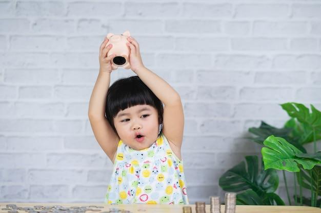 귀여운 아시아 여자 아기는 돼지 저금통에 동전을 떨어뜨리고 개념을 절약합니다.