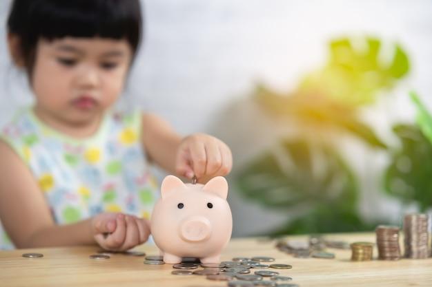 Cute asia baby girl drop coins in piggy bank,saving concept.
