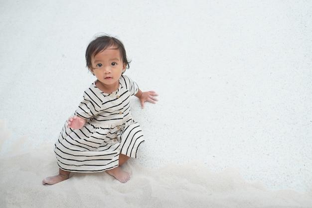 귀여운 아시아 1~2세 여자 아기가 공공 놀이터의 모래 상자에서 모래를 가지고 노는 것, 복사 공간이 있는 어린 아이를 위한 미세 운동 기술 개발