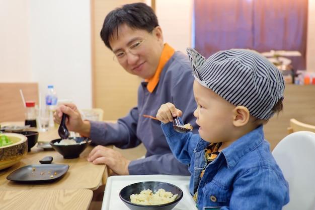 かわいいアジアの18ヶ月幼児の男の子の子供が日本のレストランで一人でフォーク&スプーンで食べ物を食べる、姫を誇りに思うお父さん、自己給餌、自助スキル、自立心を促す