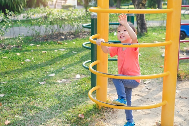 Cute asian 3 years old toddler baby boy child having fun trying to climb on climbing frame at outdoor playground