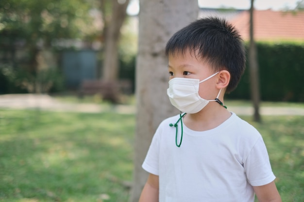 Cute asian 5 years old kid wearing protective medical face mask on nature at the park, concept of coronavirus, new normal lifestyle and air pollution pm 2.5 concept, soft and selective focus