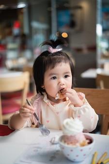 Милый азиатский ребенок ест мороженое на столе в ресторане
