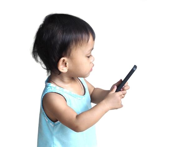 Милая азиатская девочка смотрит видео или играет сми на умном телефоне, изолированном на белой предпосылке. концепция развития ребенка.