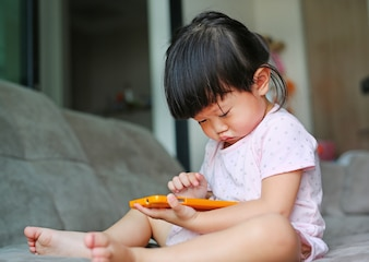Cute asian baby girl playing a smartphone and laying on gray sofa in living room