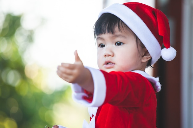 Cute asian baby girl wearing santa suit holding beautiful gift box in hand