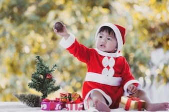 Милая азиатская девочка в костюме Санты с красивыми подарочными коробками на праздновании Рождества