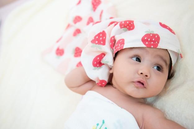 入浴後のベッドに横たわっている彼女の頭にタオルを持つかわいいアジアの女の赤ちゃん