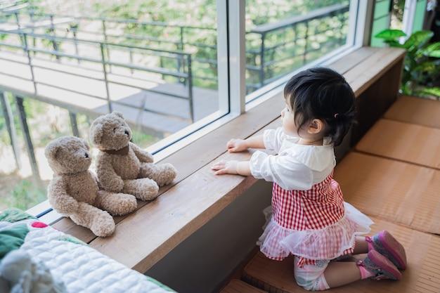 座ってカフェの窓を見てかわいいアジアの赤ちゃん