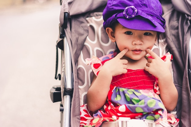 Cute asian baby sitting on baby stroller carriage and posing smiling