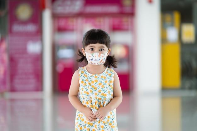 コロナウイルスを保護するためのマスクを身に着けているかわいいアジアの赤ちゃん。