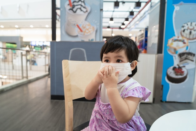 Симпатичный азиатский ребенок в хирургической маске и сидит на стуле в ожидании мороженого в ресторане