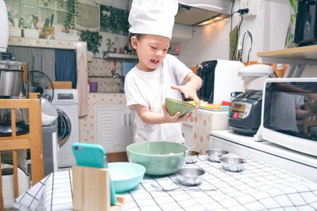 かわいいアジアの少年が朝食を調理して楽しんでいる、若いブロガーがソーシャルメディアチャンネルのvlogを作る