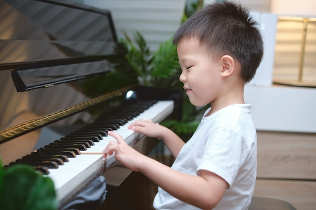 Cute asian boy playing the piano