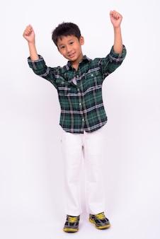 흰 벽에 녹색 체크 무늬 셔츠를 입고 귀여운 아시아 소년