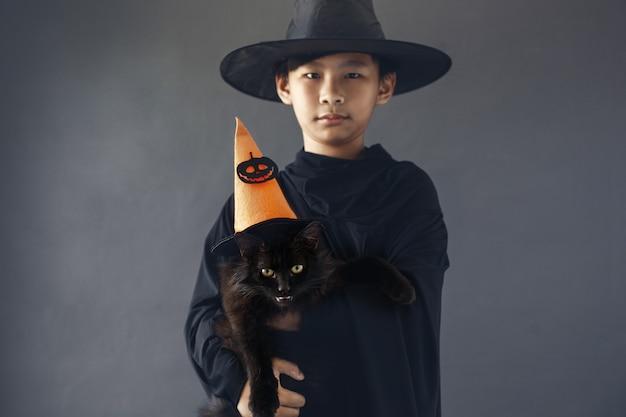 Симпатичный азиатский мальчик с кошкой в костюме хэллоуина