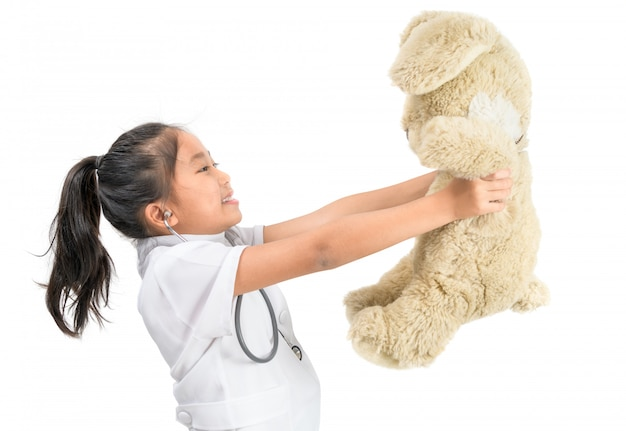 Cute asian child in doctor coat playing with teddy bear upation concept