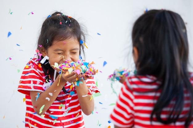 Милая азиатская девушка ребенка и ее сестра играют с красочным конфетти совместно для того чтобы отпраздновать в партии